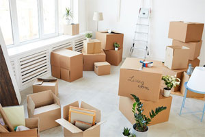Moving boxes, some taped and closed and others open sitting on the floor of a vacant, white colored living room